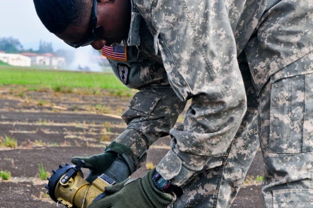 "Spc. Darin Rambert, petroleum supply specialist, Troop E, 2nd Squadron, 6th Cavalry Regiment, 25th Combat Aviation Brigade, 25th Infantry Division, attaches a fuel filter to a fuel hose on an Extended Range Fuel System, also known as the ""Fat Cow,"" during the 25th Combat Aviation Brigade, 25th Infantry Division, first joint service Forward Arming and Refueling Point Rodeo competition on Wheeler Army Airfield, Hawaii, Nov. 20."