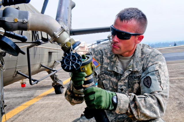 "Spc. Cory Garret, petroleum supply specialist, Company E, 2nd Battalion, 25th Aviation Regiment, 25th Combat Aviation Brigade, 25th Infantry Division, attaches a fuel hose to a UH-60 Black Hawk while setting up the micro-forward area refueling system, also known as the ""Wet Hawk,"" during the 25th CAB, 25th Infantry Division, first joint service Forward Arming and Refueling Point Rodeo competition on Wheeler Army Airfield, Hawaii, Nov. 20."