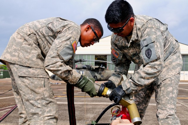"Soldiers from Company E, 2nd Battalion, 25th Aviation Regiment, 25th Combat Aviation Brigade, 25th Infantry Division, attach a fuel nozzle to a fuel hose while setting up the micro-forward area refueling system, also known as the ""Wet Hawk,"" during the 25th CAB, 25th Infantry Division, first joint service Forward Arming and Refueling Point Rodeo competition on Wheeler Army Airfield, Hawaii, Nov. 20."