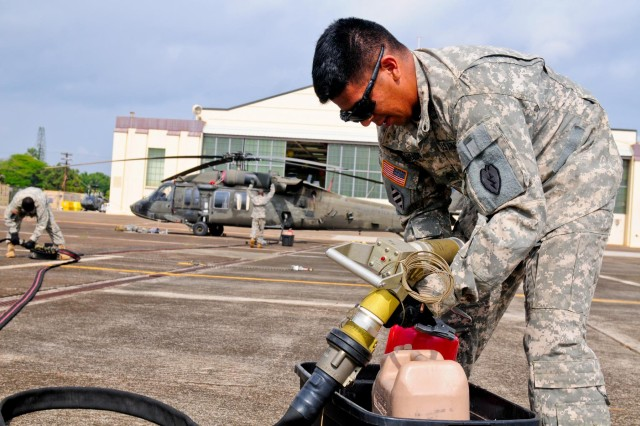 "Sgt. Greg Alvarado, petroleum supply specialist, Company E, 2nd Battalion, 25th Aviation Regiment, 25th Combat Aviation Brigade, 25th Infantry Division, inspects a fuel nozzle on the micro-forward area refueling system, also known as the ""Wet Hawk,"" during the 25th CAB, 25th Infantry Division, first joint service Forward Arming and Refueling Point Rodeo competition on Wheeler Army Airfield, Hawaii, Nov. 20."