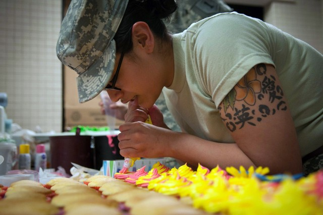 Pvt. Alexandria Perez, Co. E, 1st Bn., 28th Inf. Regt., 4th IBCT, 1st Inf. Div., pipes frosting on cupcakes Nov. 25 at Cantigny Dining Facility at Fort Riley. Perez and her fellow Army cooks baked and decorated more than 250 cupcakes late that night in preparation for the dining facility's big Thanksgiving meal the next day. (Amanda Kim Stairrett, 1st Inf. Div.)
