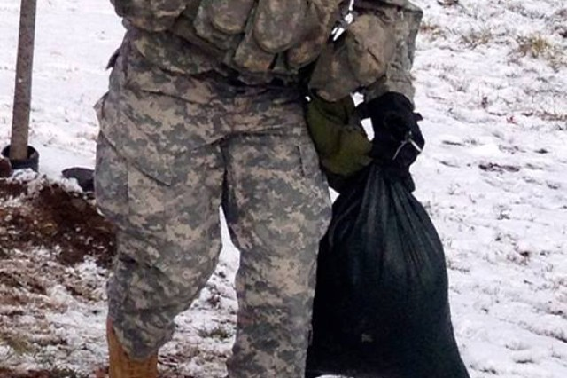 Sgt. Jesse Peterson carries two sandbags while wearing a chemical protective mask Nov. 12 during one of the challenges of Allons Avalanche on Fort Drum. The event celebrated 2nd Battalion, 15th Field Artillery Regiment, combat history while fostering section-level teamwork.