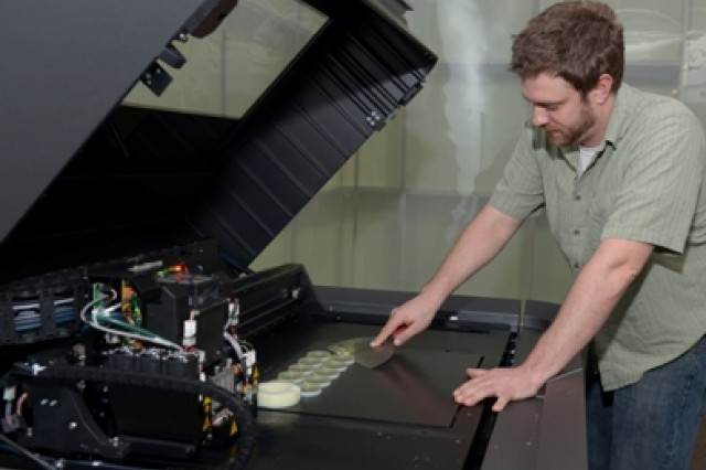 Engineering Tech Mikael Mead of Tobyhanna Army Depot removes a small production run of finished lens covers from the printing tray of a polyjet 3D printer. Three-dimensional (3D) printers produce parts out of plastic and other durable materials.  (U.S. Army photo by Tony Medici)