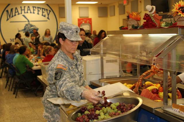 Spc. Yolanda M. Garr, a cargo specialist with the 372nd Inland Cargo Transfer Company, 129th Combat Sustainment Support Battalion, 101st Sustainment Brigade, 101st Airborne Division (Air Assault), replaces fruit on the serving line Nov. 21, at Mahaffey Middle School on Fort Campbell, Ky. The 101st Sustainment Brigade strives to be a good community partner with local schools (U.S. Army photo by Sgt. Leejay Lockhart, 101st Sustainment Brigade Public Affairs)