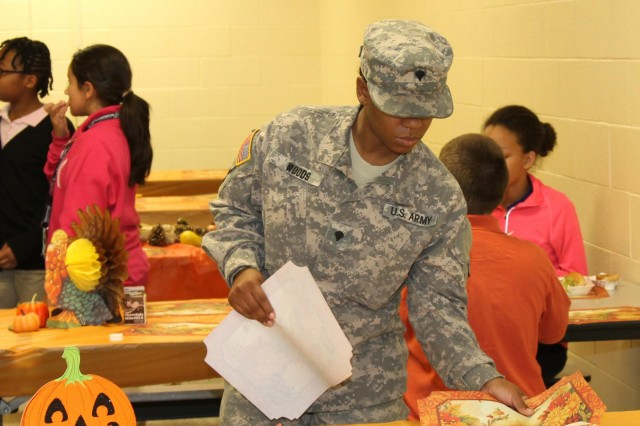 Spc. Autumn Woods, the S-3 plans clerk with Headquarters and Headquarters Company, 129th Combat Sustainment Support Battalion, 101st Sustainment Brigade, 101st Airborne Division (Air Assault), sets out new placemats during a Thanksgiving meal Nov. 21, at Mahaffey Middle School on Fort Campbell, Ky. Woods coordinated the event and worked hard to ensure its success. (U.S. Army photo by Sgt. Leejay Lockhart, 101st Sustainment Brigade Public Affairs)