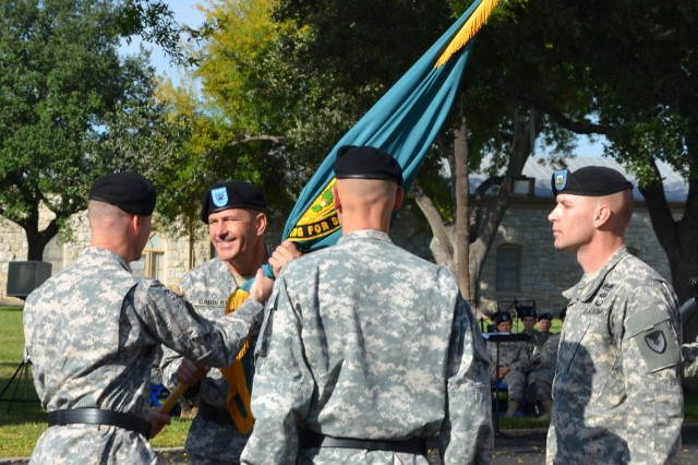 Brig. Gen. Ted Harrison, left, passes the guidon and command colors to Brig. Gen. Jeffrey Gabbert as Brig. Gen. Kirk Vollmecke and Command Sgt. Maj. Rodney Rhoades, right, look on during a change of command ceremony Dec. 2 at Joint Base San Antonio-Fort Sam Houston, Texas. Harrison is the Army Contracting Command commanding general and Gabbert is the new commanding general for the Mission and Installation Contracting Command.