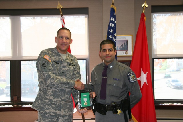 New York State Trooper Edin Herrera receives the Commander's Award for Public Service, signed by Brig. Gen. Savre and presented here by Col. Delgidio in a ceremony at Fort Hamilton on Nov. 5, 2013. Trooper Herrera was recognized for the superlative support he directly provided the U.S. Army Corps of Engineers, North Atlantic Division during Super Storm (Hurricane) Sandy recovery and response operations.