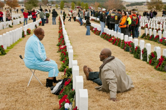 Lois Adams chats with her son, Gregory, over the headstone of her husband, former Command Sgt. Maj. Samual Adams, after placing a Christmas wreath on it, at the Central Texas State Veterans Cemetery Nov. 30, 2013. More than 1,000 volunteers from the Fort Hood/Killeen area joined family members of the fallen to place more than 5,000 wreaths on the grave markers at the cemetery. The event is organized by the Friends of the Central Texas State Veterans Cemetery and is in its eighth year. The wreaths will remain on the markers through the holiday season, to be removed the first Sunday in January.