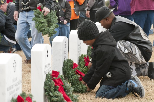 Volunteers place Christmas wreaths on grave markers at the Central Texas State Veterans Cemetery, Nov. 30, 2013. More than 1,000 volunteers from the Fort Hood/Killeen, Texas, area joined family members of the fallen to place more than 5,000 wreaths on the grave markers at the cemetery. The event is organized by the Friends of the Central Texas State Veterans Cemetery and is in its eighth year. The wreaths will remain on the markers through the holiday season, and will be removed the first Sunday in January.