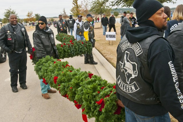 "Members of the ""Chrome Cruzers"" motorcycle club carry bundles of Christmas wreaths to be placed on grave markers at the Central Texas State Veterans Cemetery, Nov. 30, 2013. More than 1,000 volunteers from the Fort Hood/Killeen, Texas, area joined family members of the fallen to place more than 5,000 wreaths on the grave markers at the cemetery. Local biker clubs were well represented, giving the truck carrying the wreaths to the cemetery a 196-motorcycle escort. The event is organized by the Friends of the Central Texas State Veterans Cemetery and is in its eighth year. The wreaths will remain on the markers through the holiday season, and will be removed the first Sunday in January."