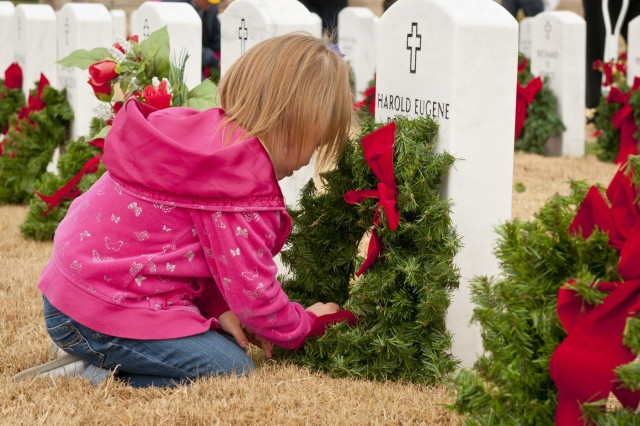 Carley Lawry, 5, places a wreath on a headstone at the Central Texas State Veterans Cemetery Nov. 30, 2013. More than 1,000 volunteers from the Fort Hood/Killeen, Texas, area joined family members of the fallen to place more than 5,000 wreaths on the grave markers at the cemetery. The event is organized by the Friends of the Central Texas State Veterans Cemetery and is in its eighth year. The wreaths will remain on the markers through the holiday season, and will be removed the first Sunday in January.