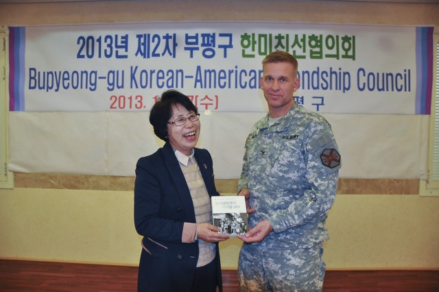 Col. Michael. E. Masley, garrison commander of U.S. Army Garrison Yongsan, right, and Hong Miyoung, mayor of Bupyeong-gu, exchange gifts during the Bupyeong-gu Korean American Friendship Council. The Bupyeong-gu KAFC works together to strengthen the ROK-U.S. alliance within the Area II military community. (U.S. Army photo by Cpl. Jung Jihoon)