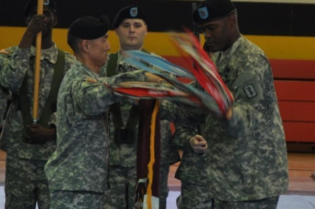 Col. Koji D. Nishimura (left) and Command Sgt. Maj. George W. Grace Jr. (right), the commander and  command sergeant major of the 30th Medical Brigade, uncase the 30th Med. Bde. colors during a ceremony on Sembach Kaserne Oct. 18. The unit re-designated from a command to a brigade as part of ongoing changes to the Army's organizational structure and i now a subordinate unit of the 21st Theater Sustainment Command.  (Photo courtesy of the U.S. Army)