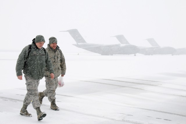 U.S. airmen with the 105th Airlift Wing, New York Air National Guard walk across the ramp at Stewart Air National Guard Base, N.Y., during a winter storm Feb. 8, 2013.