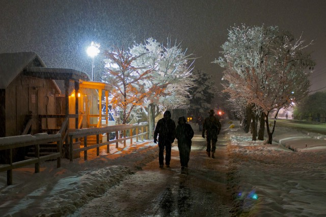 Civilian workers and soldiers stroll through a heavy snowstorm as it blankets the walkway along Disney Drive the evening of Jan. 23.