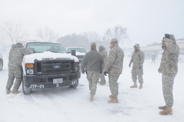 Soldiers with Joint Task Force 71 check essential equipment left outside, place snow-chains on their tires and clear the windshields of ice after a winter storm in Fort Worth, Feb. 1. JTF 71, headquartered in Austin, Texas, is in the area to support civil authorities during the weeks leading up to Super Bowl 45. Prior to departing for this mission, the units developed strategies to ensure their equipment is ready to deploy in spite of inclement weather.