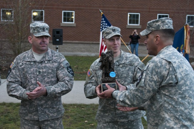 Lt. Col. Michael Trotter (right), commander of 2nd Battalion, 1st Infantry Regiment, presents the Iron Legion Trophy to the Company C commander, Capt. Marcus B. Smith, and first sergeant, 1st Sgt. Bruce Bowlan, Nov. 26, on Joint Base Lewis-McChord, Wash. The Iron Legion Competition was a grueling physical event that pitted each platoon in 2-1 Inf., 2-2 Stryker Brigade Combat Team, 7th Infantry Division, against each other as they raced against the clock to finish an array of obstacles.