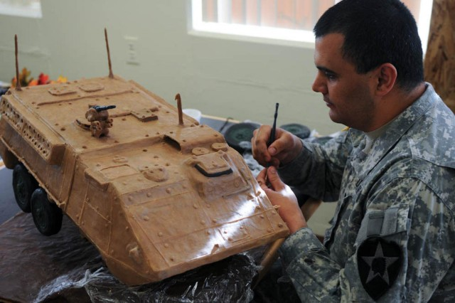 Spc. Jose Lazokafatty, food service specialist, 702nd Brigade Support Battalion, adds detail pieces onto a sculpture of a Stryker armored fighting vehicle that will be displayed at a local dinning facility on Joint Base Lewis-McChord, Wash., Nov. 26, 2013. Soldiers participated in sculpting and culinary workshops to develop new skills in creating sculptures. (U.S. Army photo by Sgt. Christopher Prows, 5th Mobile Public Affairs Detachment / Released)