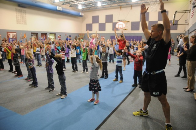 """Lt. Col. Allen Leth, commander, 1st Battalion, 8th Infantry Regiment, 3rd Armored Brigade Combat Team, 4th Infantry Divisio, participates in physical readiness training, Nov. 20, 2013, with students from Patriot Elementary. Soldiers from the """"Fighting Eagles"""" battalion conducted the modified physical readiness training sessions with the students over a three-day period, as part of the school's """"Fueling the Future"""" program."""