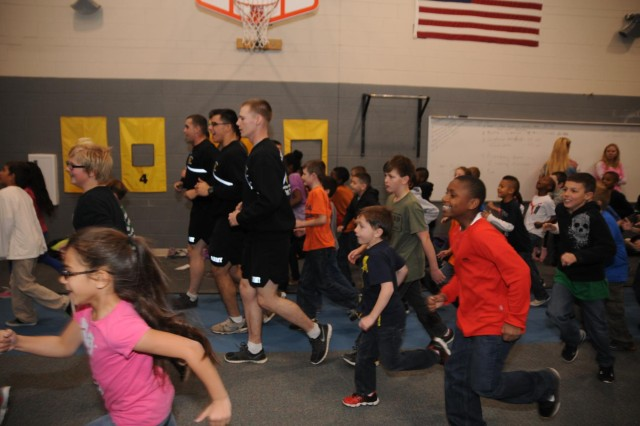 """Soldiers from 1st Battalion, 8th Infantry Regiment, 3rd Armored Brigade Combat Team, 4th Infantry Division, run with students from Patriot Elementary, Nov. 19, 2013, during a modified version of physical readiness training. The Soldiers from the """"Fighting Eagles"""" battalion conducted physical readiness training sessions with the students over a three-day period, to allow each student the opportunity to attend."""