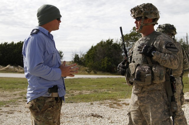 "A Soldier (right) with Company C, 2nd ""Stallion"" Battalion, 8th Cavalry Regiment, 1st ""Ironhorse"" Brigade Combat Team, 1st Cavalry Division, meets with a police officer role-played by a Soldier assigned to 2nd ""Thunderhorse"" Bn., 12th Cav. Reg. of the Ironhorse Bde. during a Soldier Leader Engagement scenario, Nov. 14, at Fort Hood, Texas. Soldiers negotiated conditions of their patrol with village leaders and police officers during the exercise. Soldiers of the Ironhorse Bde. participated in Ironhorse Rampage Nov. 4 to 22, conducting various training exercises in preparation for an upcoming rotation to the National Training Center."