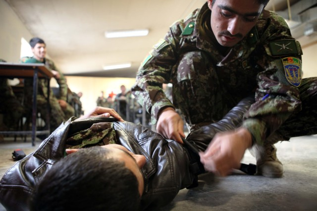 An Afghan National Army Infantry Officer with the 203rd Corps applies a tourniquet to a simulated casualty during a First Aid Class on Forward Operating Base Thunder, Paktiya province, Dec. 2, 2013. The class is intended to refresh Afghan National Army officers on the basic life saving techniques employed in combat situations. (U.S. Army photo by Spc. Ryan D. Green/Released)