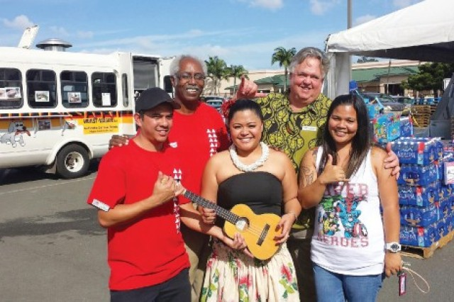 Gregory McGruder (back row, left), Schofield Barracks Commissary store director, takes a break to share a photo opportunity with participants and sponsors.