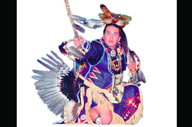 """Eagle Boy Coe performs a dance that depicts a sport popular in American Indian culture called """"stick ball"""" during the National American Indian Heritage Month celebration at the post theater Nov. 20."""