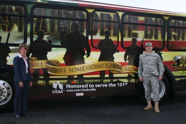 "Clarksville, Tenn., Mayor Kim McMillan (left) and 101st Airborne Division (Air Assault) Senior Commander Brig. Gen. Mark Stammer pose by the brand new ""101st Tribute Bus"" that was unveiled Wednesday afternoon at the Clarksville Transit System Bus Fleet."