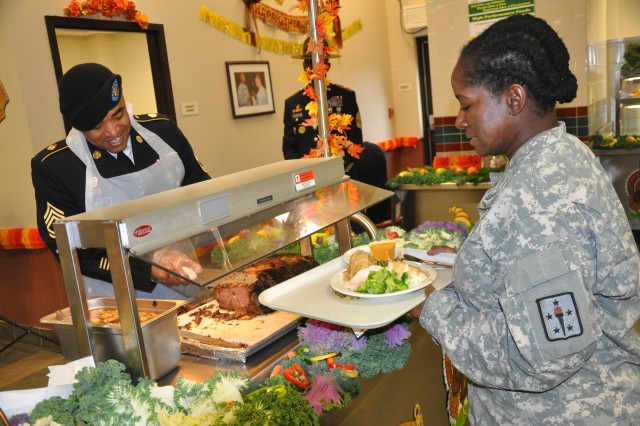 Capt. Jacqueline Murray-Bonno, an instructor at the Adjutant General School, waits as a Soldier carves a roast during a Thanksgiving meal at the U.S. Army Drill Sergeant School dining facility last Wednesday.