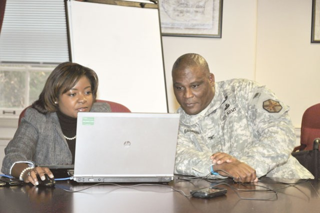 Brittany Brown (left), U.S. Army social media manager, types as Fort Belvoir Garrison Commander Col. Gregory D. Gadson looks on during an Army Facebook chat Nov. 26.