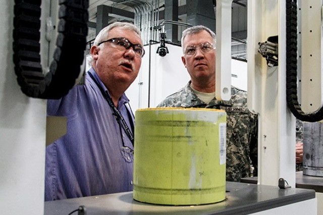 Allen Rosser, an Anniston Munitions Center Multiple Launch Rocket System Recycle Center supervisor, discusses the operations of the MLRS with Col. Lee Hudson, commander of Blue Grass Army Depot, during his tour of ANMC Dec. 2.