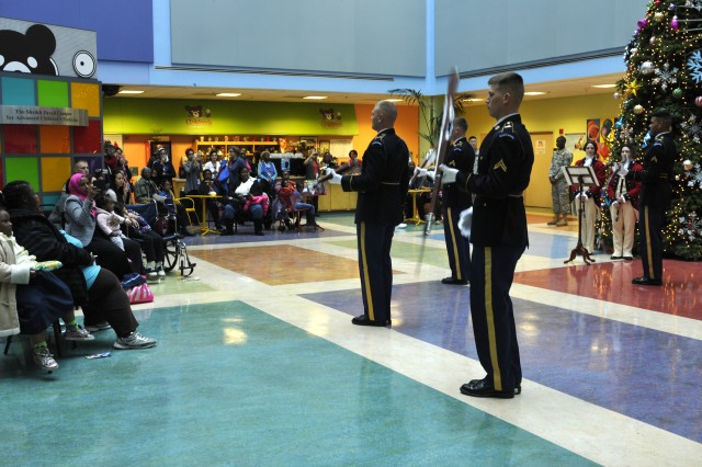 Soloists from the U.S. Army Drill Team, 3d U.S. Infantry (The Old Guard), perform a routine at the Children's National Medical Center in Washington, D.C., Dec. 3, 2013. The performance helped bring some cheer to the children and their families who may have to spend the holidays in the hospital. (U.S. Army Photo by Staff Sgt. Megan Garcia)