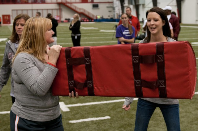 "Fort Riley mom Berni Kappelprepares to tackle the mat as fellow mom Stacie Dumas assists during the USA Football ""Heads Up"" clinic on Dec. 3 at the University of Kansas Hospital Training Complex near Arrowhead Stadium in Kansas City, Mo. The clinic was highlighted by former Kansas City Chiefs players and a talk about the NFL's lead to increase safety at all levels of football led by NFL commissioner Roger Goodell."