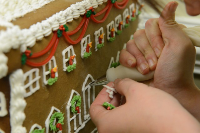 Spc. Samantha Poe touches up the gingerbread house of the U.S. Capitol, at the Army Executive Dining Facility at the Pentagon, Dec. 5, 2013.