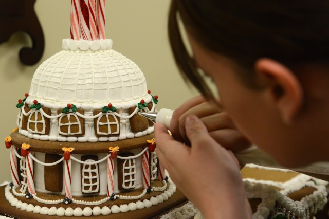 Spc. Samantha Poe touches up the dome of the gingerbread house of the U.S. Capitol, at the Army Executive Dining Facility at the Pentagon, Dec. 5, 2013.