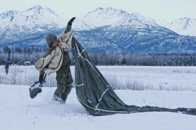 """Spc. James Klein, a paratrooper with the 4th Infantry Brigade Combat Team (Airborne), 25th Infantry Division, secures his parachute for follow-on movement Dec. 4, 2013 at the Malemute Drop Zone at Joint Base Elmendorf-Richardson, Alaska. The 4-25th partnered with Bravo Company, 1st Battalion, 52d Aviation Regiment from Fort Wainwright for the mission. Spartan paratroopers exited the """"Sugar Bears'"""" CH-47 Chinook Helicopters, demonstrating their forced entry capabilities. (U.S. Army photo by Staff Sgt. Jeffrey Smith/Released)"""
