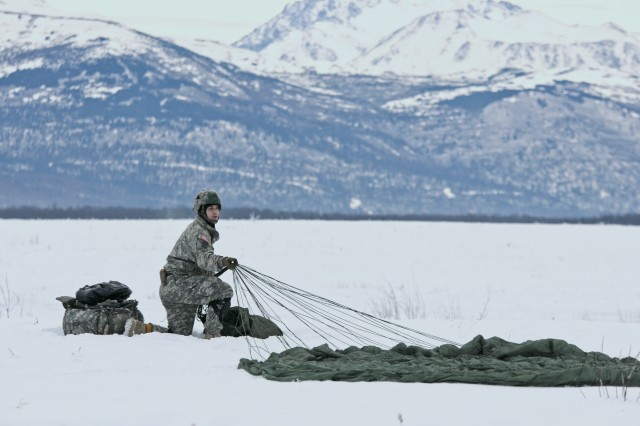 Sgt. 1st Class Christopher Russon, an infantry platoon sergeant with the 1st Battalion, 501st Infantry Regiment, 4th Infantry Brigade Combat Team (Airborne), 25th Infantry Division, gathers his parachute after landing Dec. 4, 2013  at the Malemute Drop Zone at Joint Base Elmendorf-Richardson, Alaska. Russon was making his final jump with the unit before his upcoming permanent change of station move. (U.S. Army photo by Staff Sgt. Jeffrey Smith/Released)