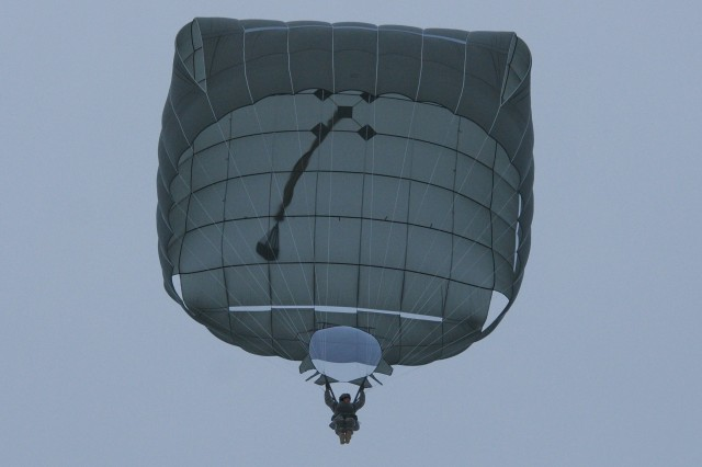 """A paratrooper with the 4th Infantry Brigade Combat Team (Airborne), 25th Infantry Division, descends to the ground under the canopy of a T-11 parachute Dec. 4, 2013 at the Malemute Drop Zone at Joint Base Elmendorf-Richardson, Alaska. The 4-25th partnered with the """"Sugar Bears,"""" Bravo Company, 1st Battalion, 52d Aviation Regiment from Fort Wainwright, Alaska for the day's mission. Spartan paratroopers exited CH-47 Chinook helicopters, demonstrating the Spartan Brigade's unique ability to conduct airborne forced entry operations. (U.S. Army photo by Staff Sgt. Jeffrey Smith/Released)"""