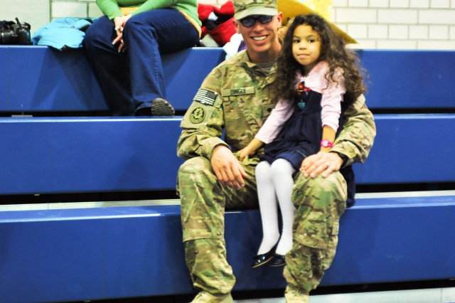 Spc. James Dingle, a fire direction controller assigned to Fires Squadron, 2d Cavalry Regiment holds his daughter, Jaymi, as he poses for a photo after returning home from Afghanistan, Nov 23, 2013. James returned from Afghanistan where he was deployed in support of Operation Enduring Freedom.