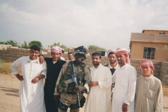 """UNDISCLOSED LOCATION, Iraq """" Then Sgt. 1st Class Michael Young, an infantryman and squad leader with 3rd Battalion, 187th Infantry Regiment, 101st Airborne Division, has his picture taken with local villagers in 2002. Young's unit visited the village to conduct a meeting to assess the villager's needs for food, water and electricity. Young is currently a chief warrant officer 3, a UH-60 Black Hawk helicopter pilot and unit safety officer with 2nd Battalion (Assault), Task Force Knighthawk, 10th Combat Aviation Brigade. (Courtesy photo)"""