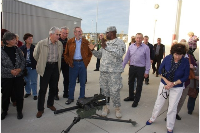 """GRAFENWOEHR, Germany """" Spc. Christain Ugwvanyi of Headquarters and Headquarters Company, 18th Combat Sustainment Support Battalion, 16th Sustainment Brigade, 21st Theater Sustainment Command, shows members of the Freihung Seniors Club an Mk19 40-mm automatic grenade launcher during a visit Oct. 22.  The 18th CSSB partner with the Germany city of Freihung.  Despite the close proximity of U.S. Army Garrision Bavaria to Freihung, its residents rarely have an opportunity to see the daily lives of the U.S. Soldiers.  (U.S. Army photo by Sgt. Jonathan Morillo, 18th Combat Sustainment Support Battalion, 16th Sustainment Brigade, 21st TSC Public Affairs)"""