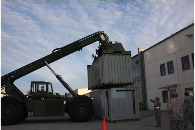"""GRAFENWOEHR, Germany """" Spc. Jamie Flowers with the 1st Inland Cargo Transfer Company, 18th Combat Sustainment Support Battalion, 16th Sustainment Brigade, 21st Theater Sustainment Command, moves a 4,000-pound empty 20-foot shipping container by operating a 37-foot tall rough-terrain container handler in order to demonstrate its capabilities to members of the Freihung Seniors Club Oct. 22 The 18th CSSB partner with the Germany city of Freihung.  Despite the close proximity of U.S. Army Garrision Bavaria to Freihung, its residents rarely have an opportunity to see the daily lives of the U.S. Soldiers.  (U.S. Army photo by Sgt. Jonathan Morillo, 18th Combat Sustainment Support Battalion, 16th Sustainment Brigade, 21st TSC Public Affairs)"""