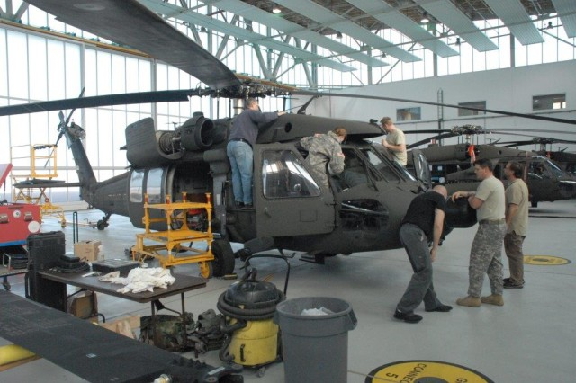 An aircraft maintenance crew on Clay Kaserne, Wiesbaden, conducts a pre-flight inspection on a UH60A Black Hawk helicopter.
