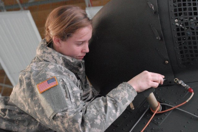 Spc. Stephanie Horne, 1st Battalion, 214th Aviation Regiment, 12th Combat Aviation Brigade re-installs tail rotor gearbox covers.
