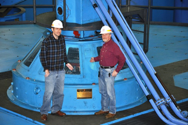 From left, Jamie Holt, power plant specialist, and Jamie James, project manager, stand atop U.S. Army Corps of Engineers Nashville District's recently repaired Barkley Hydropower Plant Unit 1 generator Kuttawa, Ky. The unit suffered a phase-to-ground fault resulting in a fire that damaged the 32.5 Megawatt generator wirings in Dec. 19, 2010. The $11.5 million, major repair project began Aug. 15, 2012 when contractor employees lifted the 270-ton assembly by crane and placed it on a nearby pedestal for repair by National Electric Coil from Columbus, Ohio. Unit 1 was placed back on line Nov. 18, 2013. (USACE photo by Fred Tucker)