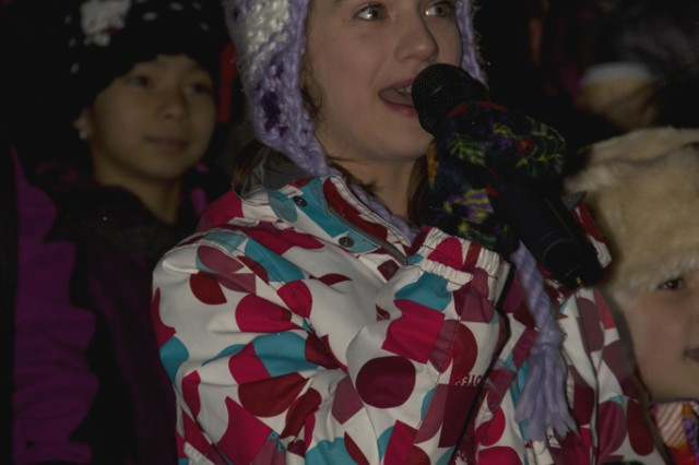 An Illesheim Elementary student gets her chance to wow the crowd while singing Christmas carols at the Storck Barracks tree-lighting ceremony Dec. 6.