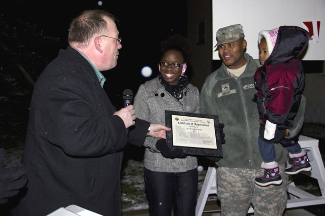 Kevin Griess presents the Bright Family with the USAG Ansbach Military Family of the Year at the Storck Barracks tree-lighting ceremony Dec. 6.
