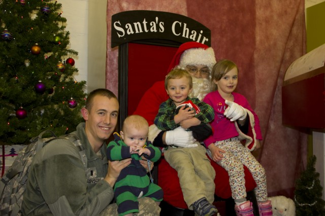 A family gets their picture taken with Santa after the Christmas tree lighting ceremony at Storck Barracks Dec. 6.