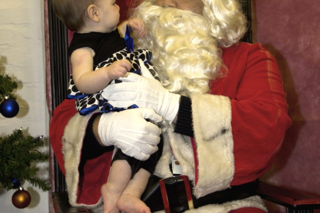 A child gets her picture taken with Santa after the Storck Barracks tree-lighting ceremony Dec. 6.